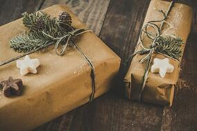 photo-of-two-brown-wrapped-gifts-on-wooden-table